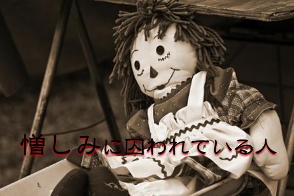 赤い影付きの文字で憎しみに囚われている人と書かれた人形の白黒写真
