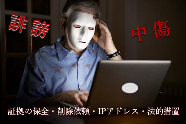 白い仮面を付けた男が暗い部屋でノートパソコンに向かっている写真