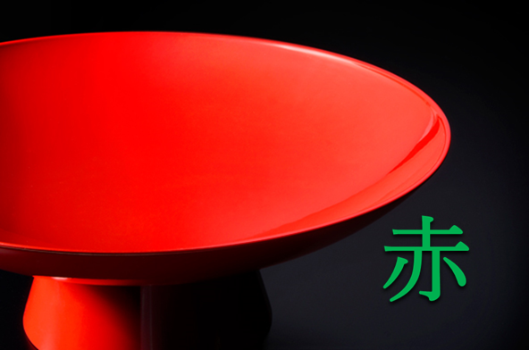 黒い背景に赤い漆塗りの盃の写真