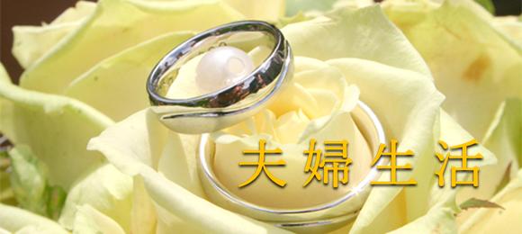 クリーム色がかった白いバラに1粒の真珠とペアペアの結婚指輪が乗っている写真