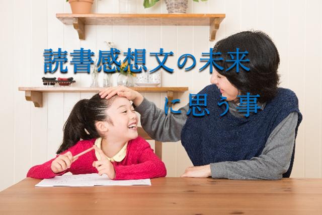 読書感想文を書いている女に子の頭をお母さんが撫でている笑顔の写真