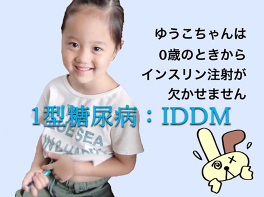 5歳のゆうこちゃんがインスリンの注射器をお腹に当てている笑顔の写真