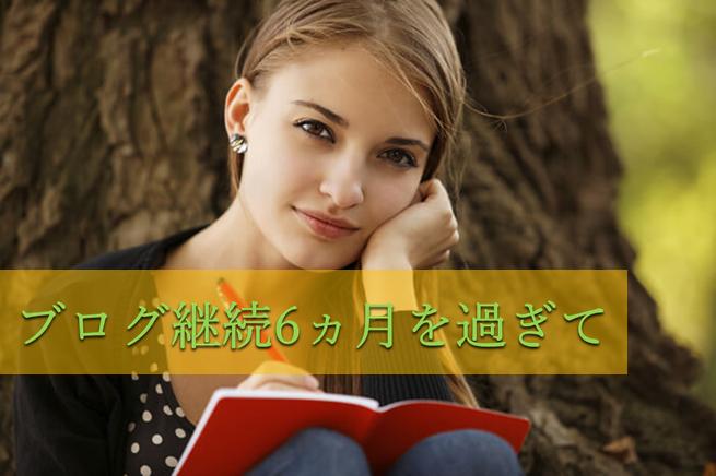 太い木の根元に腰掛けて赤い手帳に書きながら満足そうに微笑んでいる女性の写真