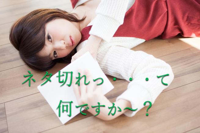 フローリングにに転んで読書している赤いスカートに白いセーターの女の子