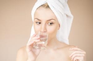 タオルのターバンを巻いてコップの水を口に入れている女性の写真
