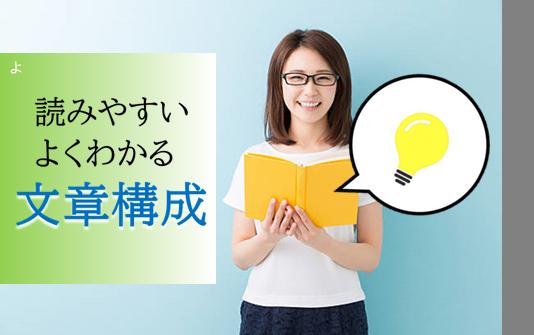 黄色い本を持って眼鏡をかけたセミロングの女性がひらめいて笑っている画像