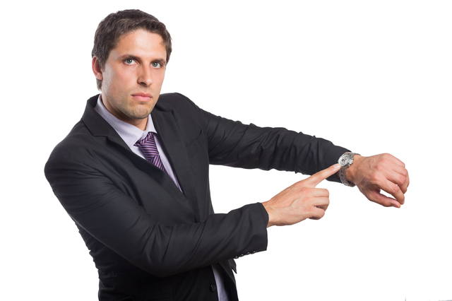 Portrait of a serious businessman showing his wristwatch over white background