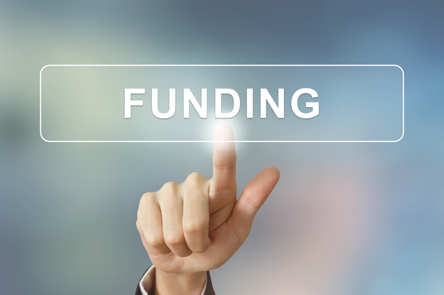 business hand clicking funding button on blurred background