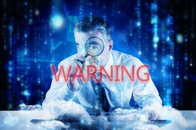 The word warning and mature businessman examining with magnifying glass against lines of blue blurred letters falling