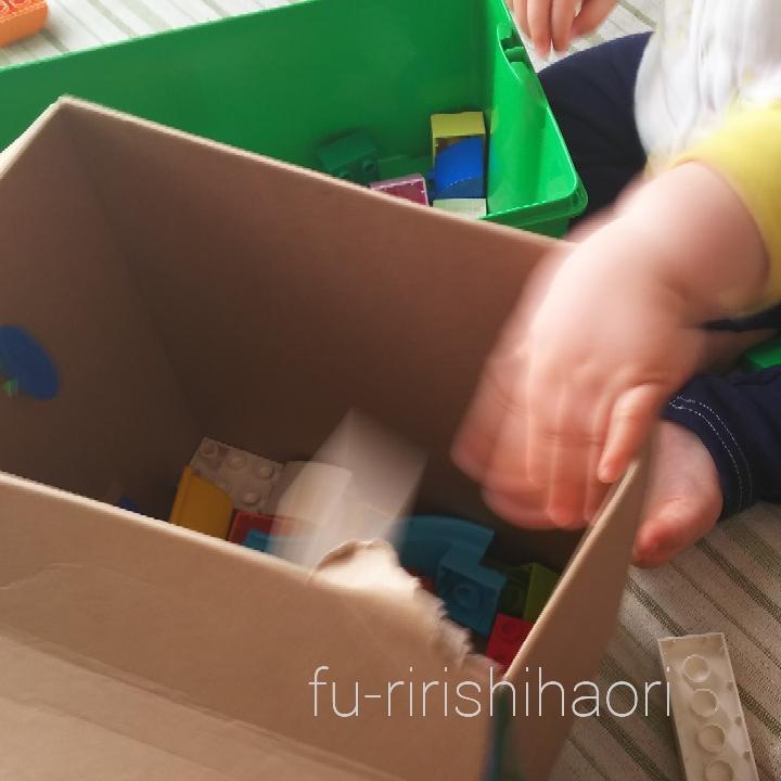 レゴデュプロを箱から箱へ移す子供の手