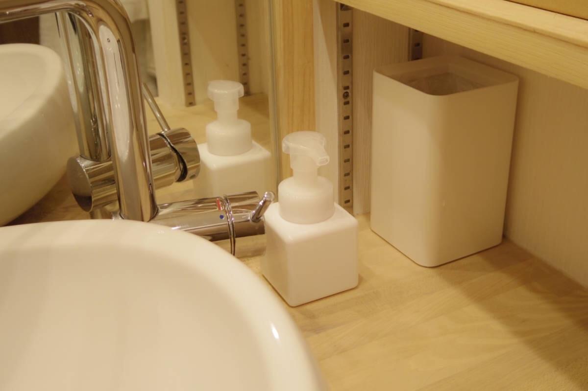 白い陶器の洗面ボウルと、白い泡ポンプに入ったハンドソープ、卓上ゴミ箱にぴったりな無印良品のトイレポット