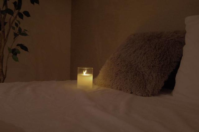 枕元のクッション脇におかれたキャンドル風のライト。本物のように揺らめく明かりでリラックスできます