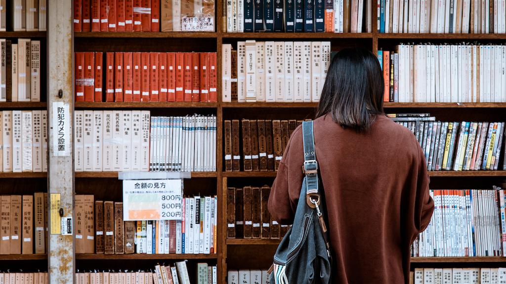 図書館で女性が本を立ち読みしている