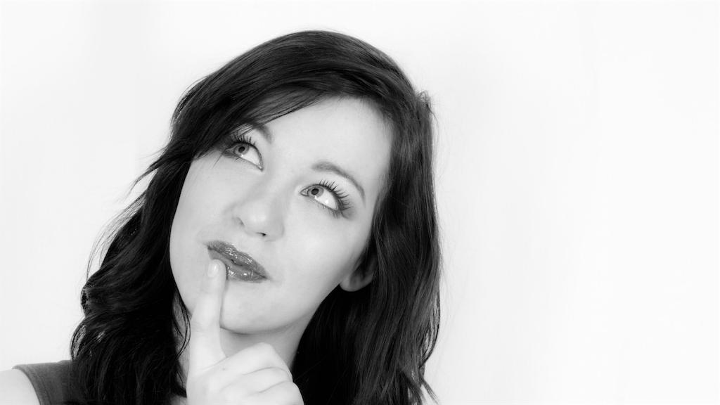 女性が人差し指を唇に当て、考えている