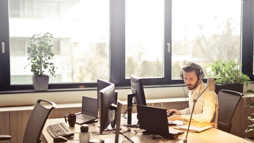 ヘッドホンを付けた男性がパソコンを見ながら集中して作業をしている