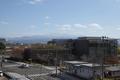 警察庁舎から見る鶴岡の町並みと月山の図