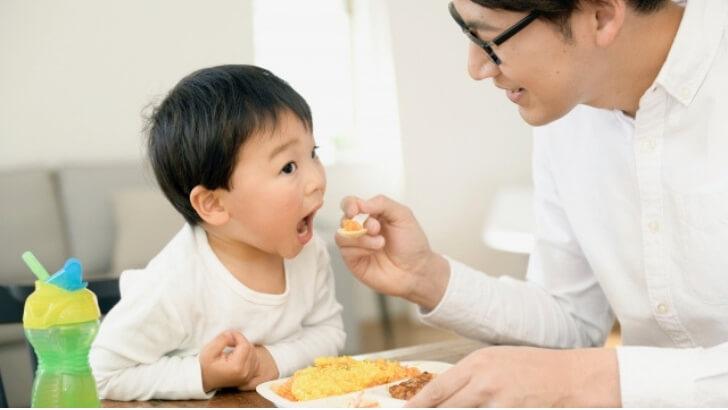 子どもにご飯を食べさせる男性