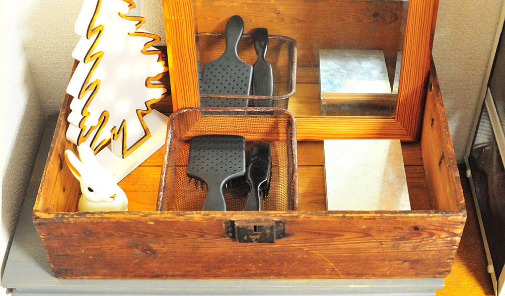 ドレッサー代わりの木の箱にはブラシやアクセサリー缶を入れている