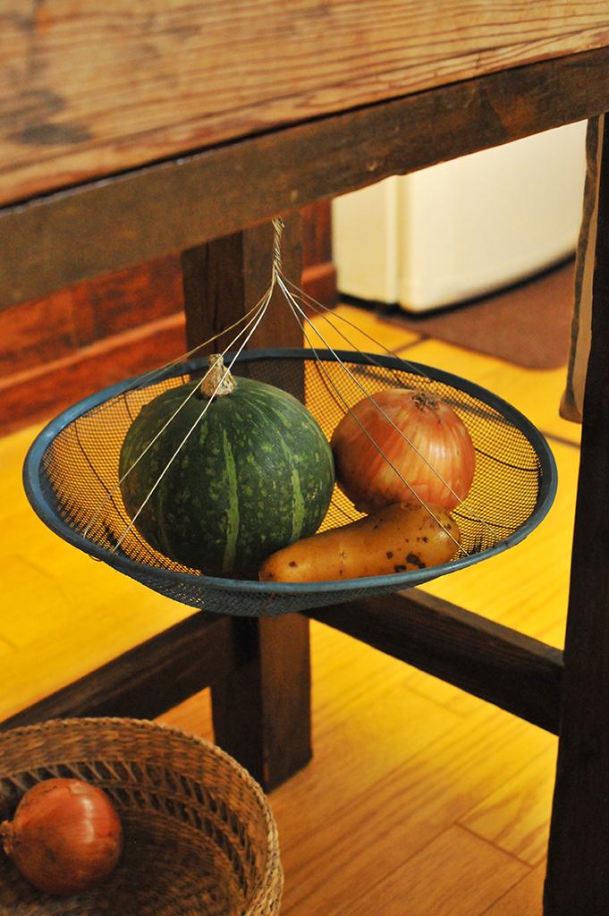 野菜カゴにした針金をつけて台所の机の下に吊るしたザル