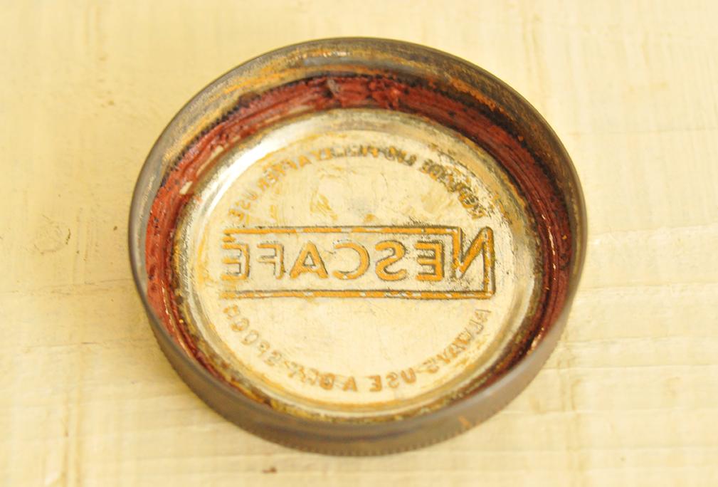 古い缶の商品ロゴが裏に浮き出ているフタ