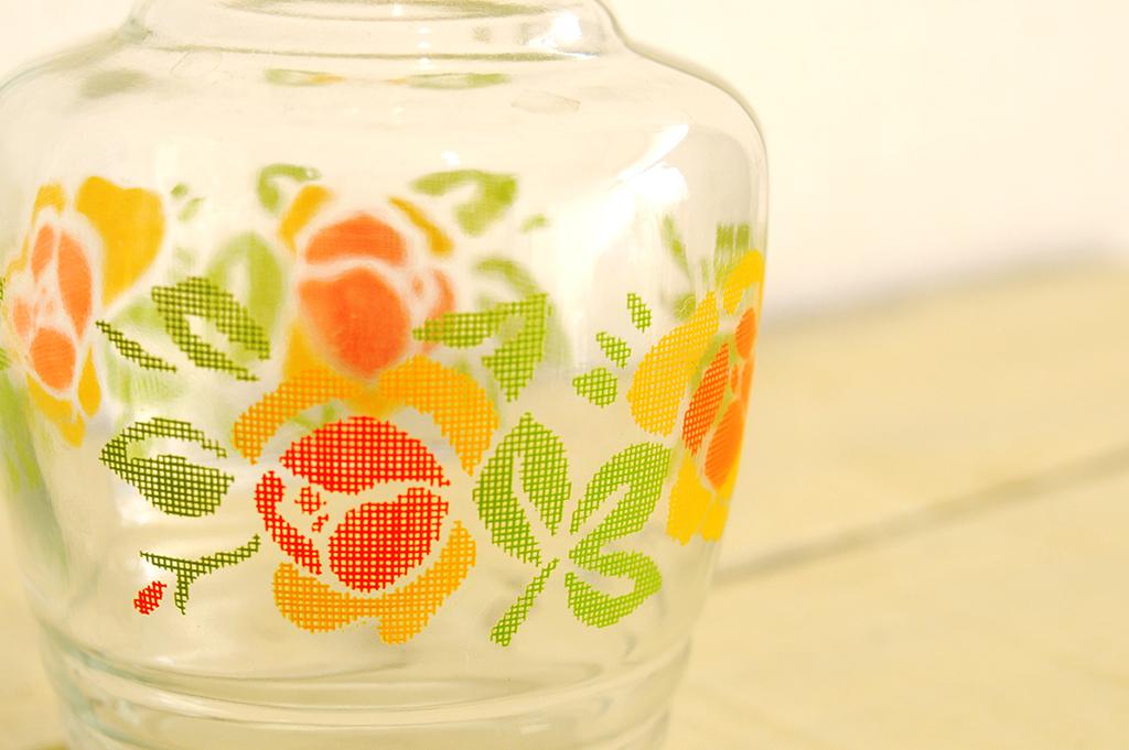 刺繍のステッチのように描かれたオレンジと黄色の花のイラスト模様ピッチャー