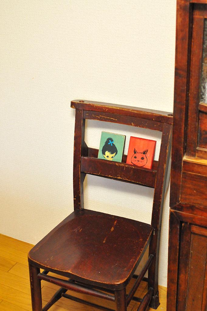 チャーチチェアに飾った緑のイラストと赤い猫のイラストの木製イラストボード