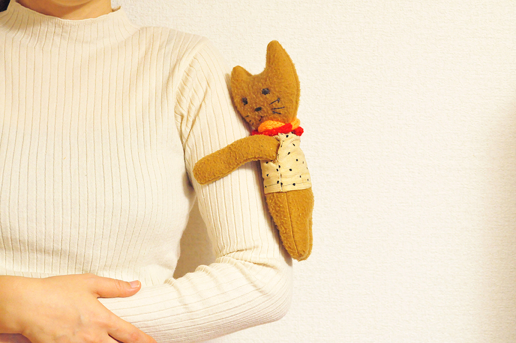 両腕をのばして腕にひっつく抱っこ人形の猫ちゃん