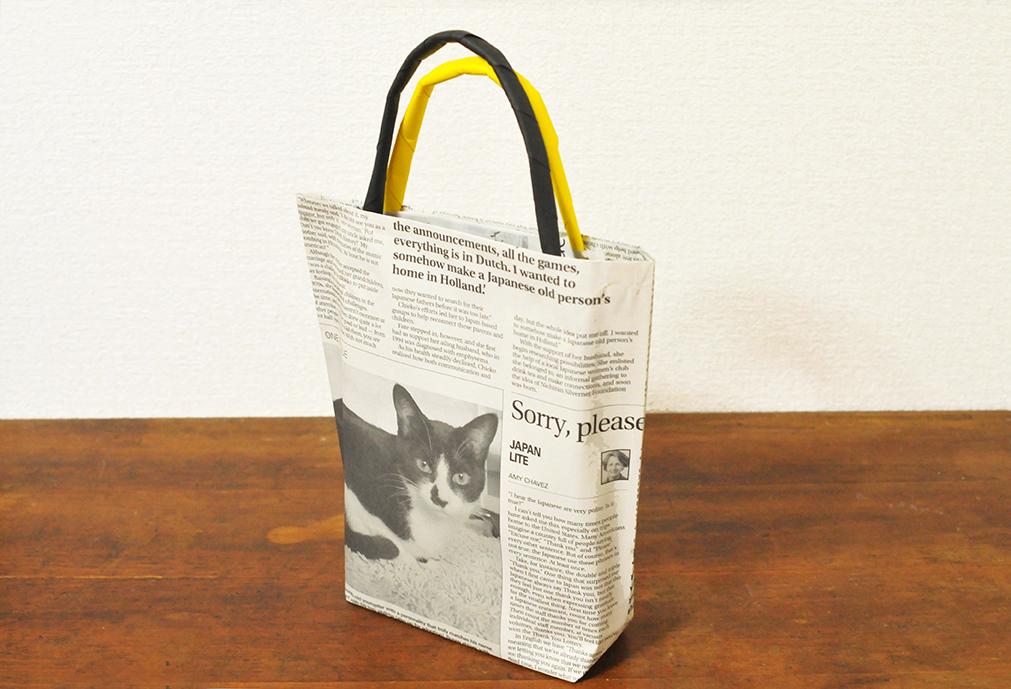 取手をカラー用紙でアレンジした新聞紙バッグは猫写真記事がポイント