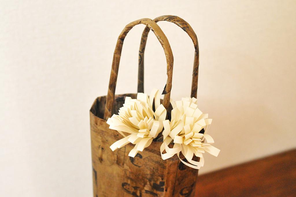 コピー用紙で作った花を新聞紙で作ったワインバッグに飾る