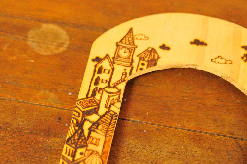 電気ペンヒーティングツールで木製フレームに細かい絵を描く
