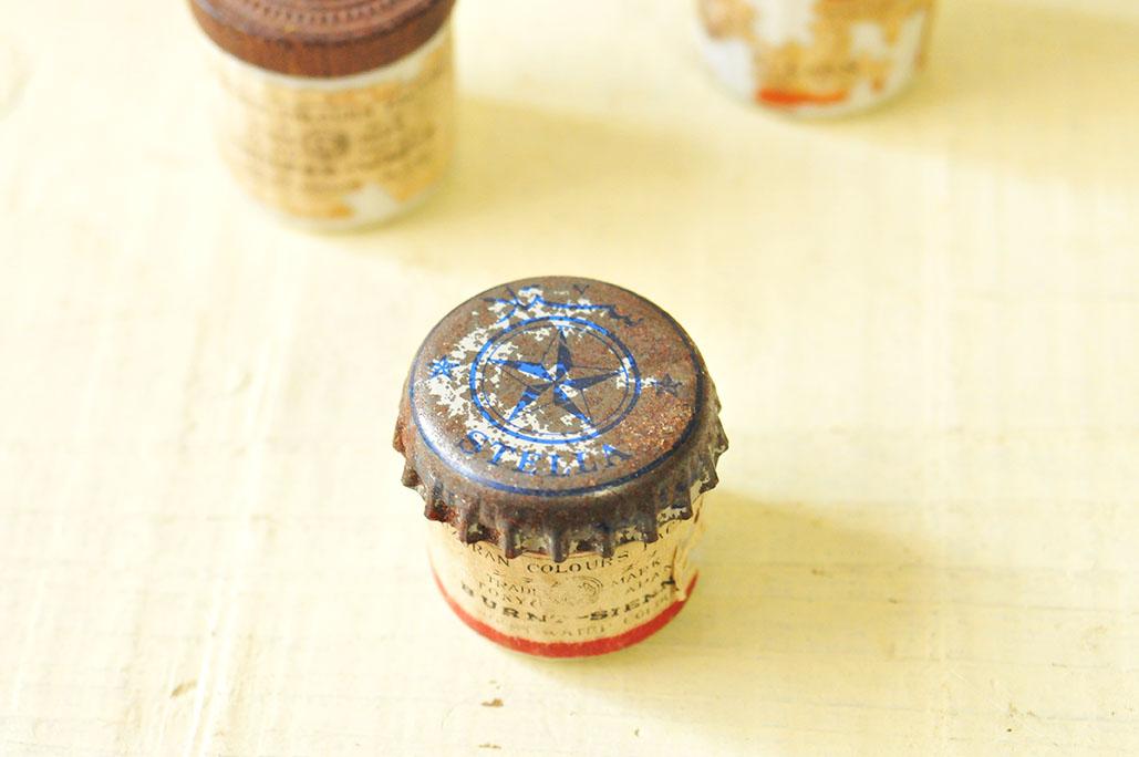 海外で拾った瓶のフタを古い絵具瓶のフタ代わりにする