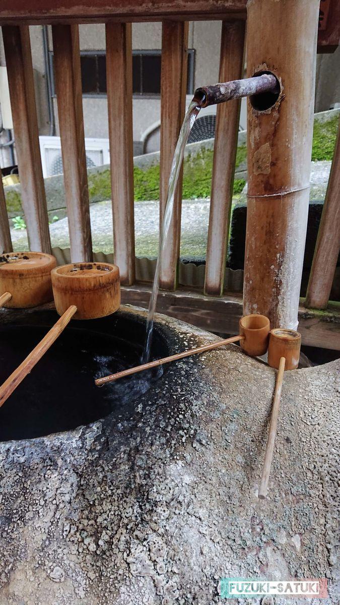 柄杓で温泉を汲む 写真