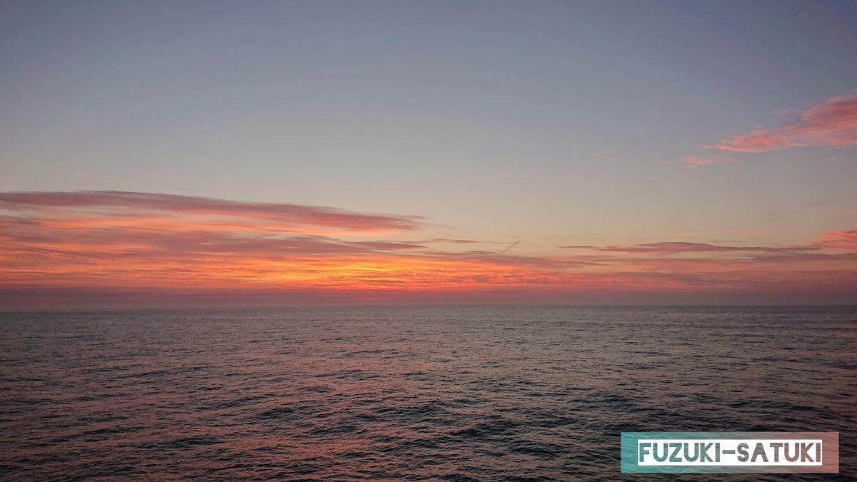 夜明け前の茜色に染まる空の写真