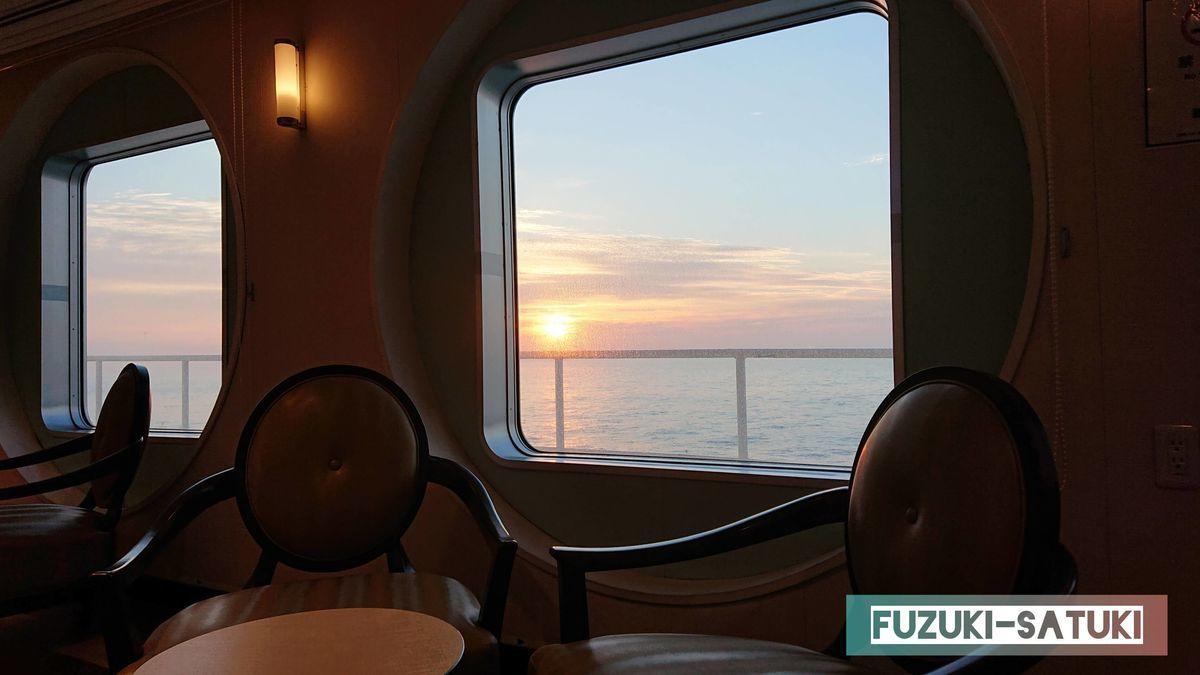ロビーの窓から望む日の出の写真