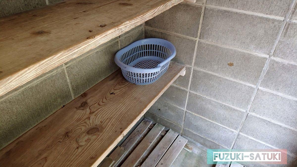 木造の脱衣所の中 籠が1個だけある