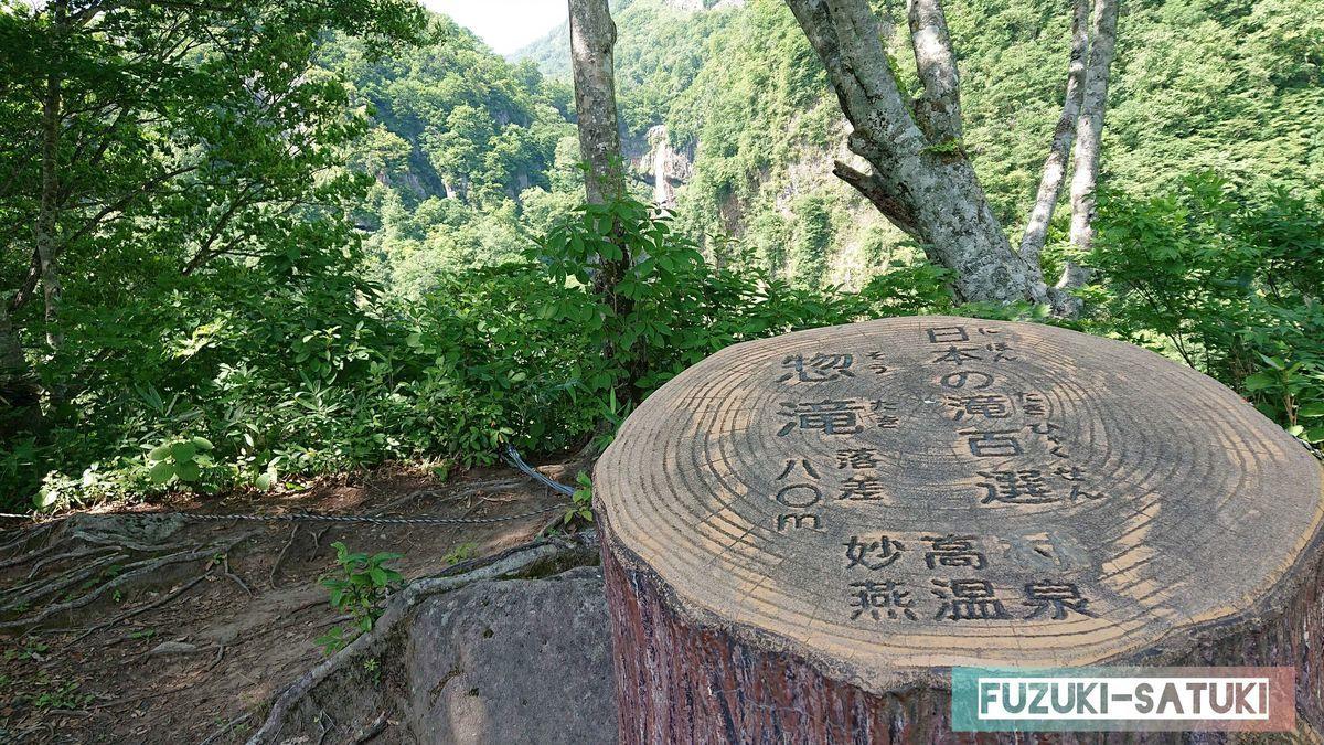 切株に日本の滝百選 惣滝と書かれている。遠くに滝が見える