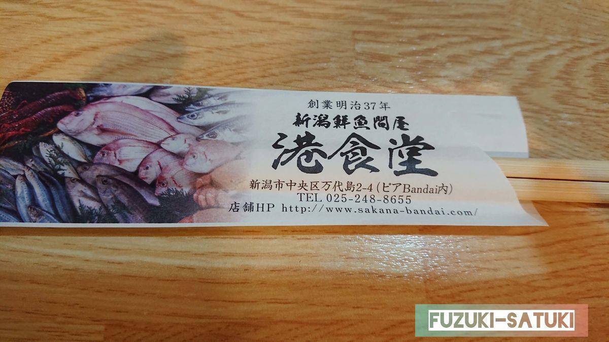 席に着くと店員さんが持ってきてくれる箸。鮮魚の写真と店名、住所等の詳細が載せられている。