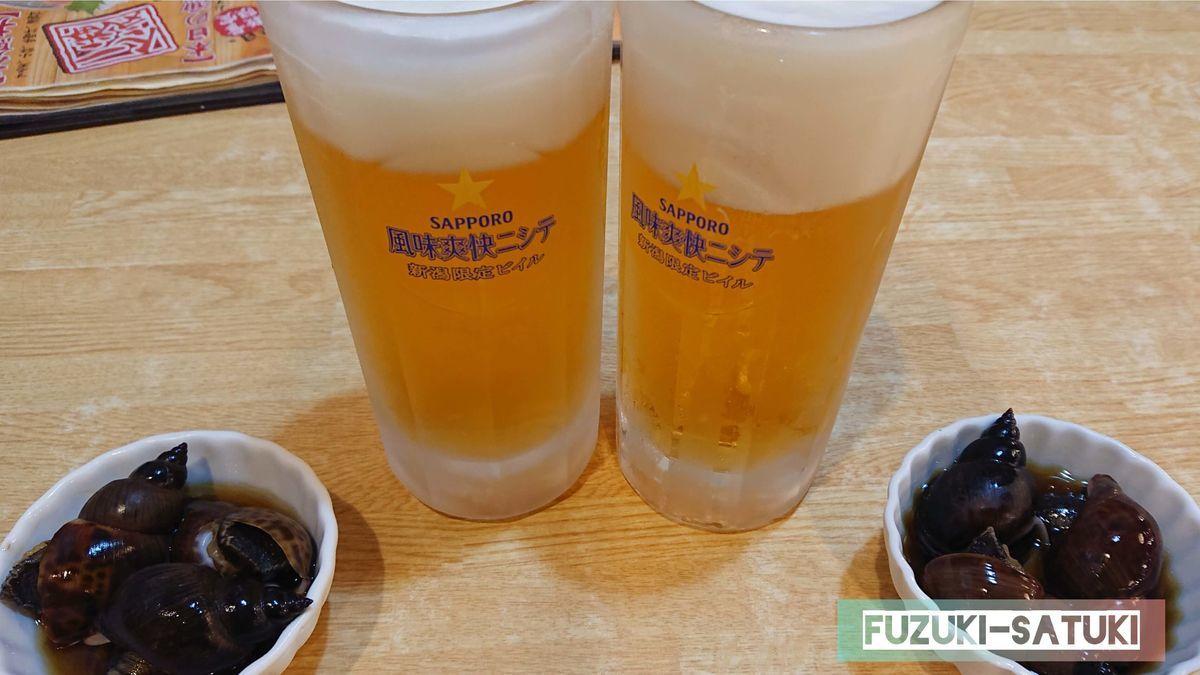 まずはビールで乾杯。「風味爽快ニシテ 新潟限定ビイル」と書かれている。お通しはバイ貝。