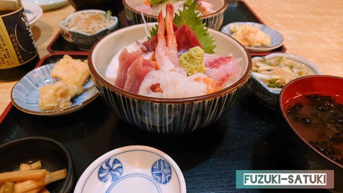 海鮮丼。イカの天ぷらと漬物、小鉢に岩海苔のお味噌汁が付いている贅沢な一品。