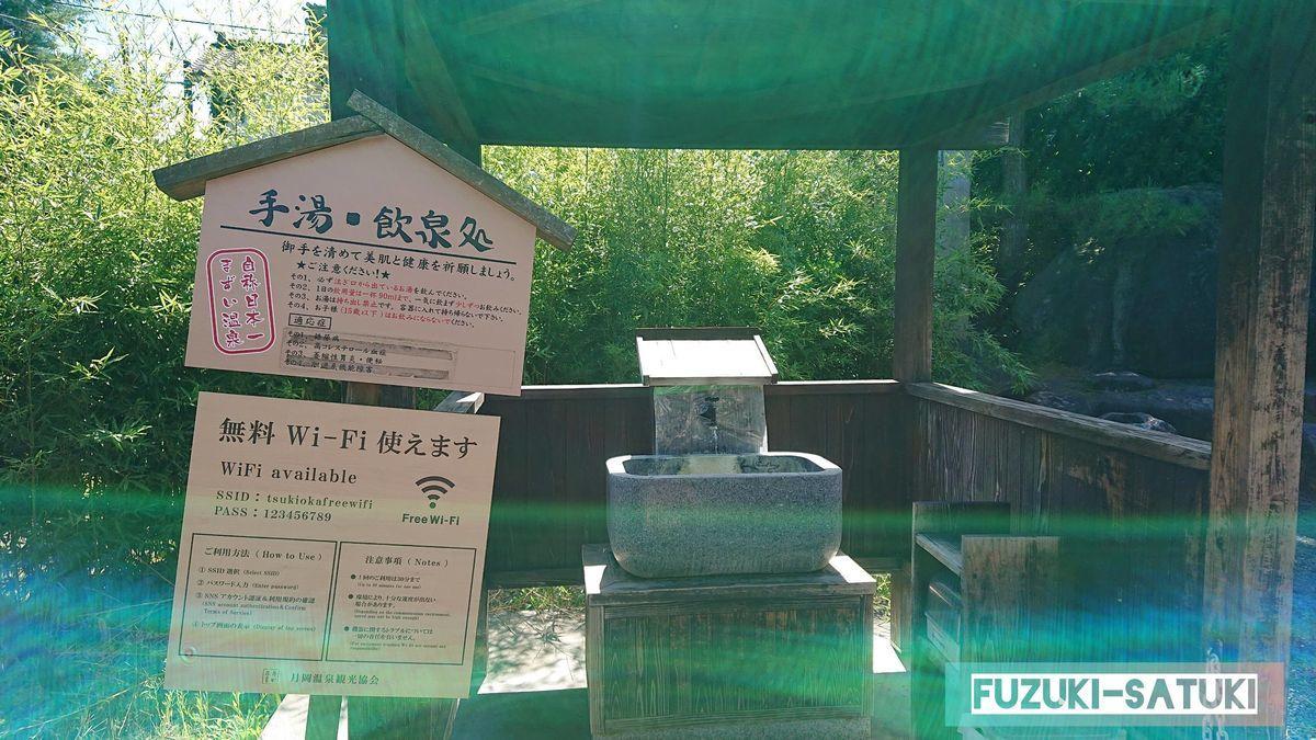 手湯・飲泉処という看板と、横の蛇口から源泉が流れ出ている