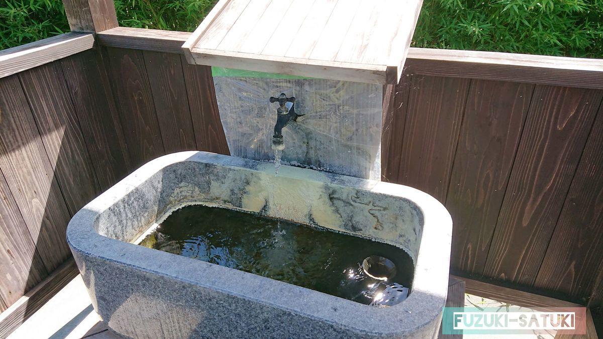 飲泉所 硫黄で錆びた蛇口から若干黄色を帯びた透明のお湯がドバドバと注がれている