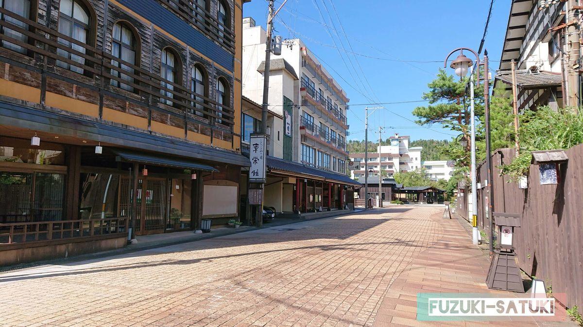 月岡温泉街から、足湯(あしゆ湯足美)へ向かう通り道と、澄んだ青空。両側に並ぶ、古くもしっかりと佇む建物からは、むしろ力強さを感じるほど。
