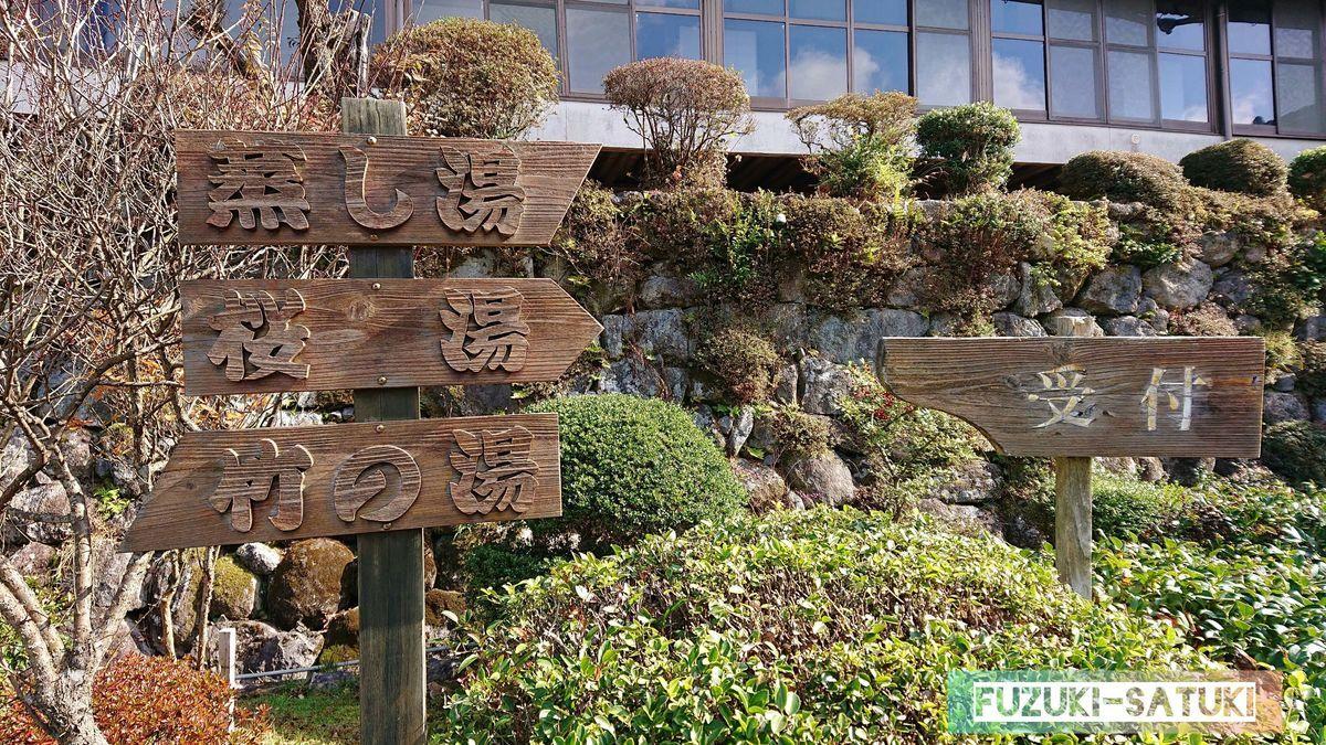 雰囲気のある、木製の案内板。受付は向かって左、桜湯と蒸し風呂は右となる。