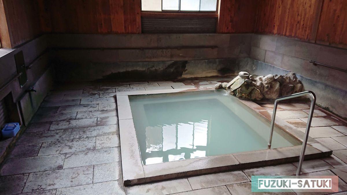 桜湯 男湯 浴室内 石造りの床に、温かみのある木の壁板、石の浴槽内には乳白色の綺麗なお湯が注がれている