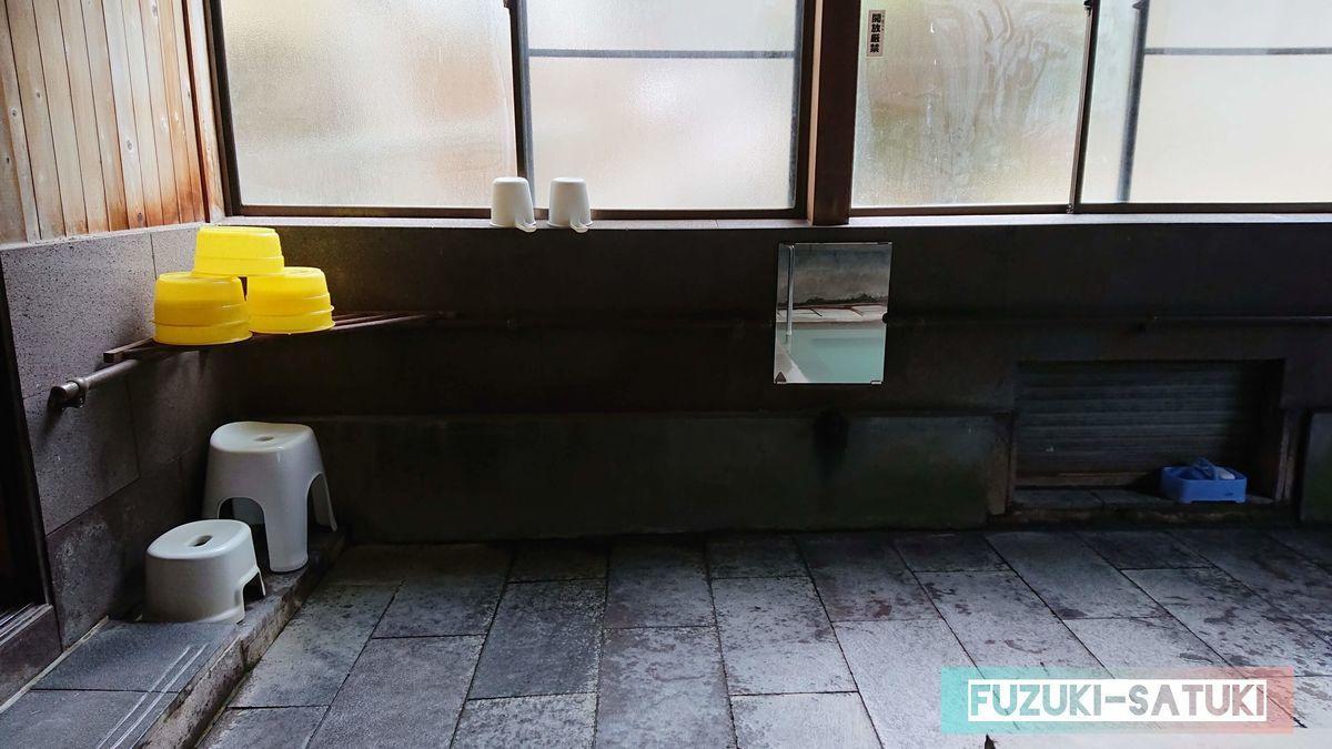 備え付けのケロリン桶とプラスチック製の風呂椅子。石鹸がひとつ置かれている