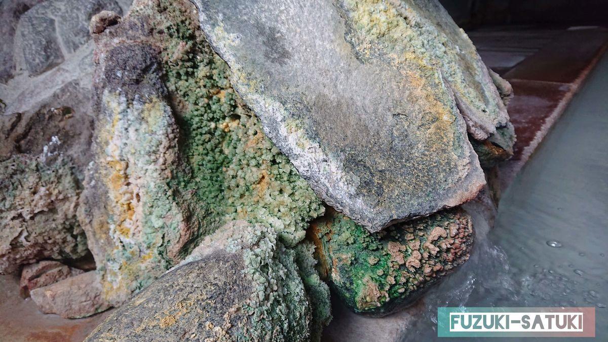源泉湯口 温泉成分の結晶が、白、緑と多くこびり付いて形作っている