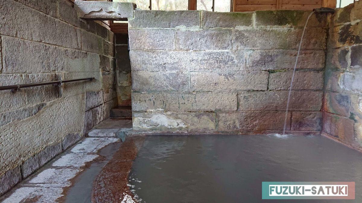 竹の湯 浴室 内湯には高い位置から源泉が注がれている。浴槽内は墨のような濃い灰色、淵からは泥が流れ出ている