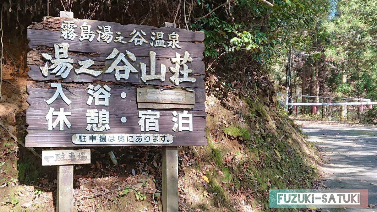 湯之谷山荘 霧島湯之谷温泉の木製の看板 入浴、休憩、宿泊、駐車場は奥にあります と書かれている