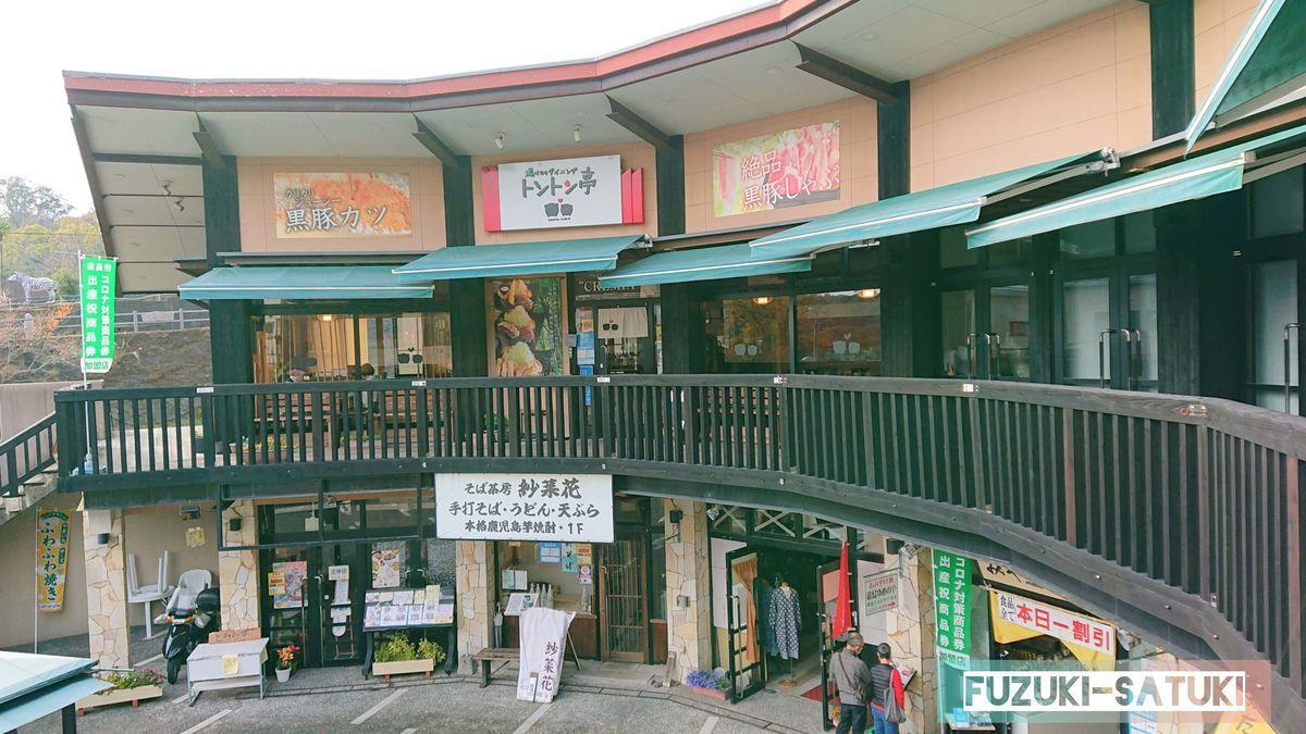 霧島温泉市場の店舗を写したもの。2階建ての建物で、2階には地物黒豚をメインとした飲食店、1階は蕎麦屋とお土産屋が店を連ねる。