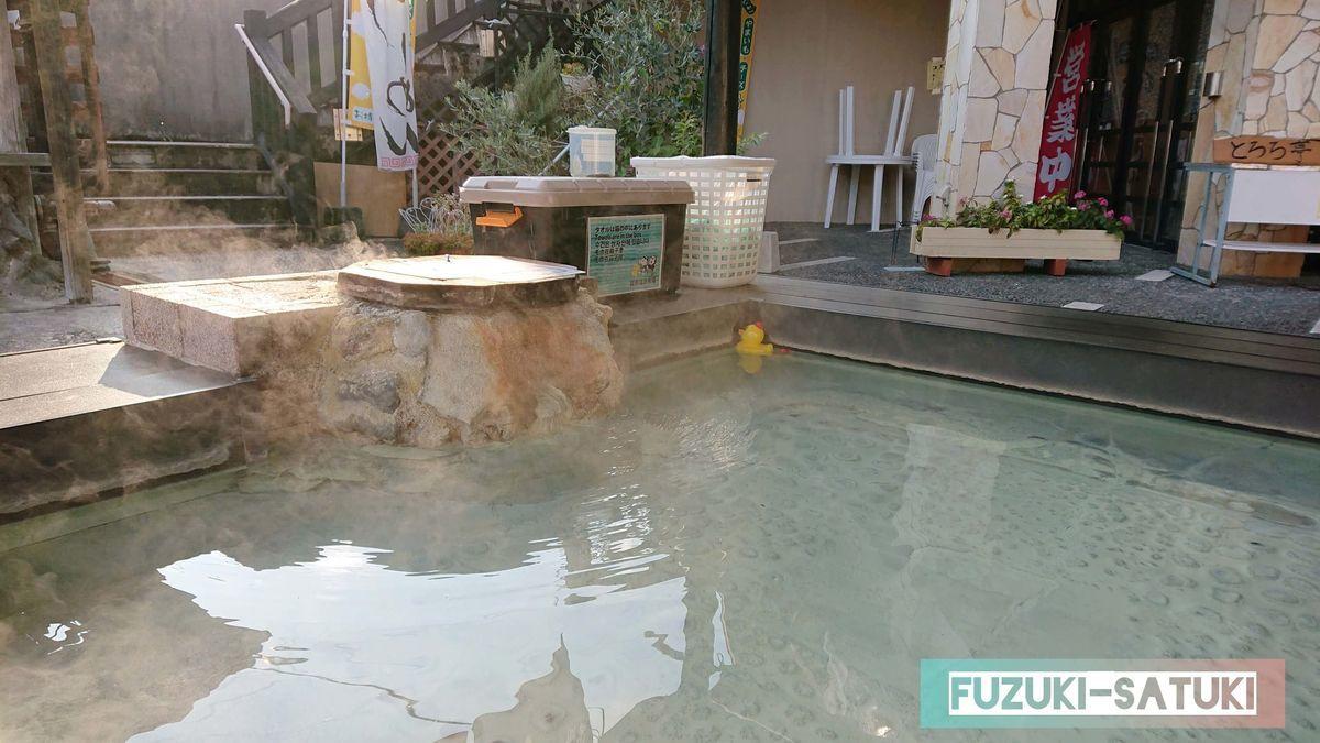 ほんわかと硫黄香る足湯の源泉口。見るからに柔らかそうなお湯だとわかる。透明に近い乳白色のお湯。